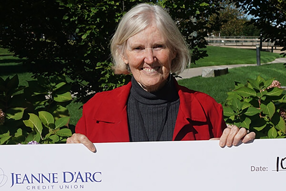 Elizabeth Kidd holding a check from Jeanne D'Arc Credit Union