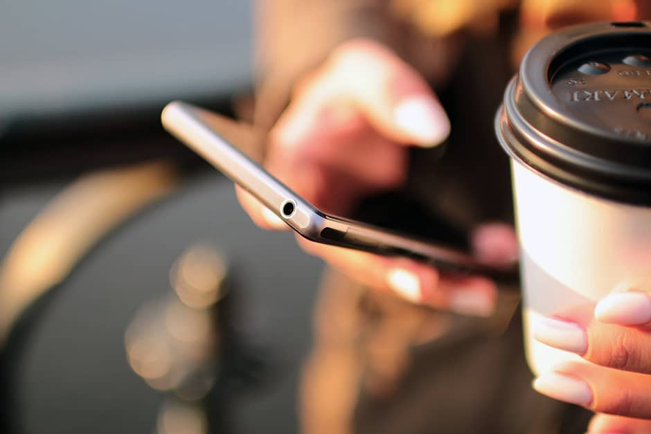 Hand holding a mobile device and a cup of coffee-to-go