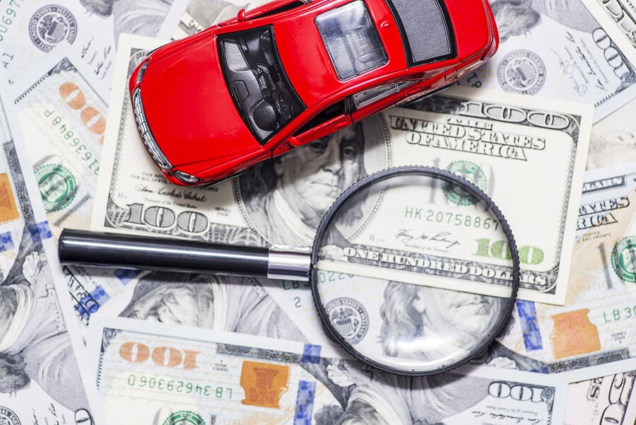 a magnifying glass, a stack of money, and a car