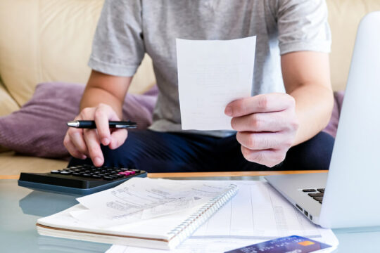 a man budgeting and calculating numbers to apply for a personal loan