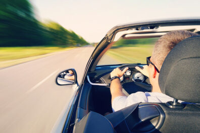 a man driving his convertible on an open road
