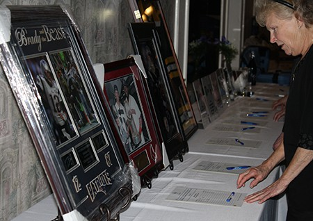 Woman looking at items up for auction at the Jeanne D'Arc Credit Union annual fundraiser