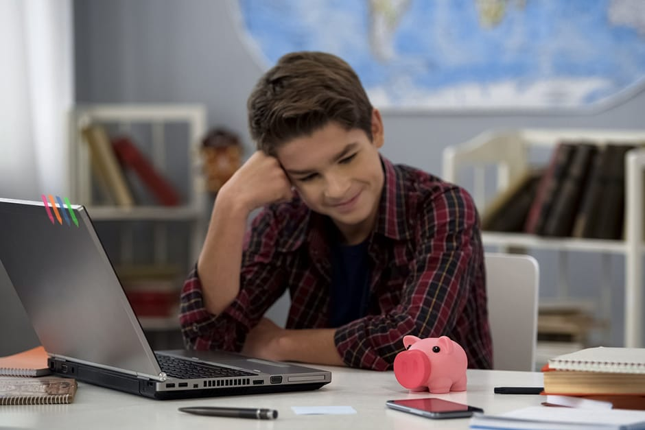 Boy sitting at laptop staring at a piggy bank