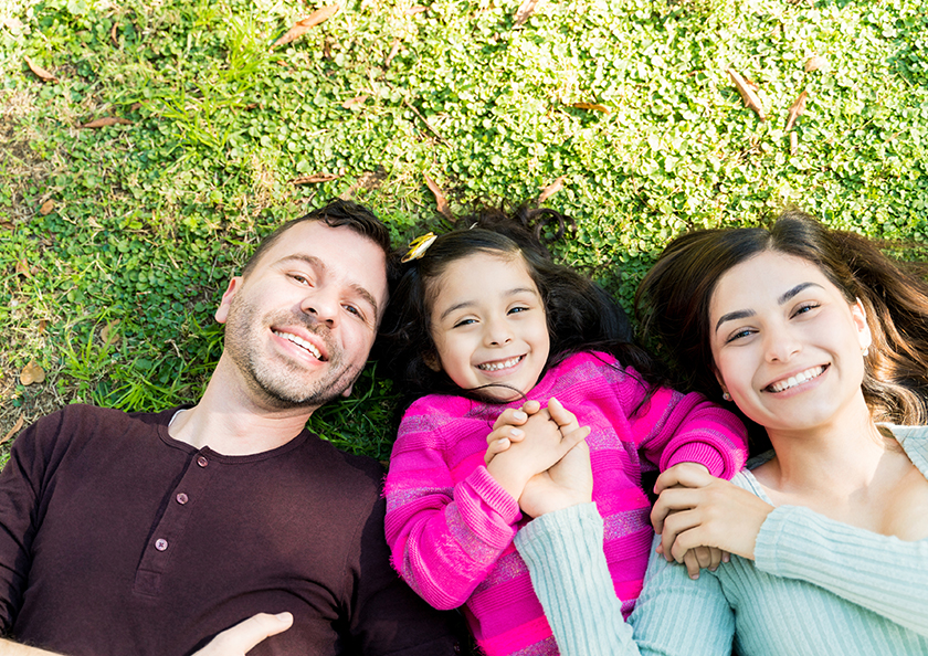 family-laying-on-grass-hero