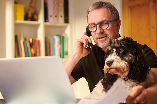 man-budgeting-online-with-dog-mcti1
