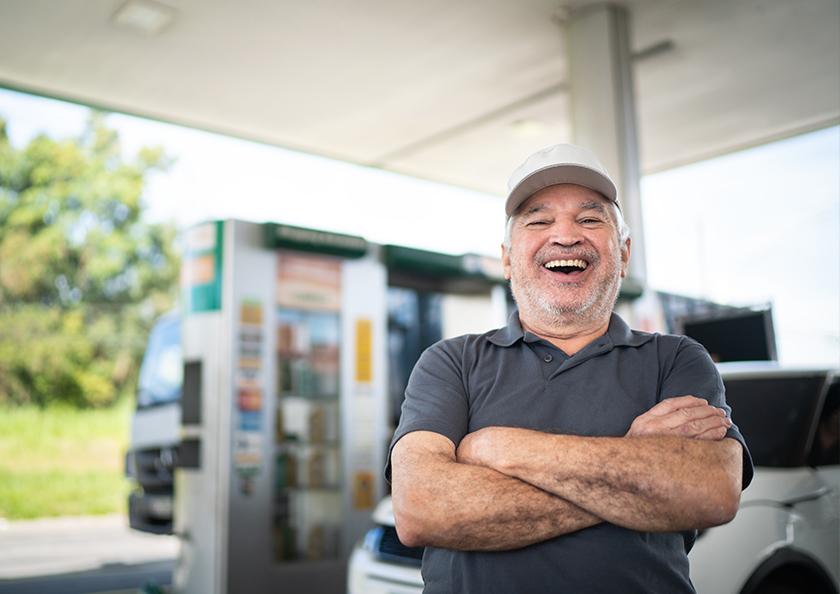 man-smiling-while-putting-gas-in-rv-Hero
