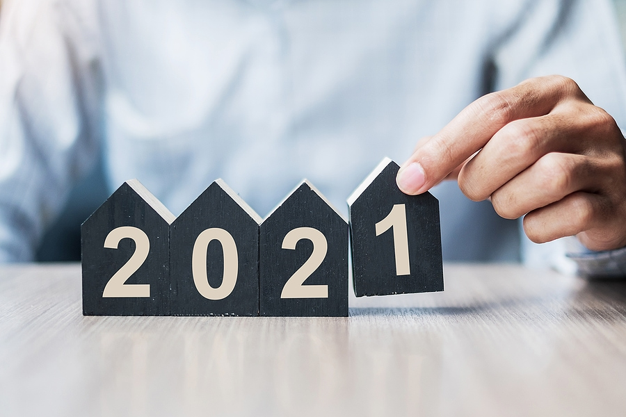 a man placing number blocks shaped like houses to display 2021