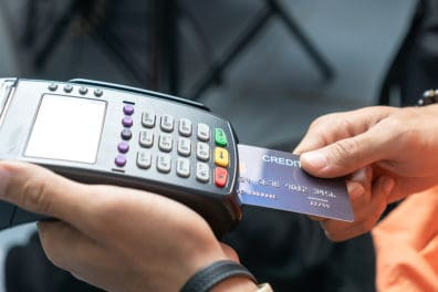 A credit card being inserted into a payment processor