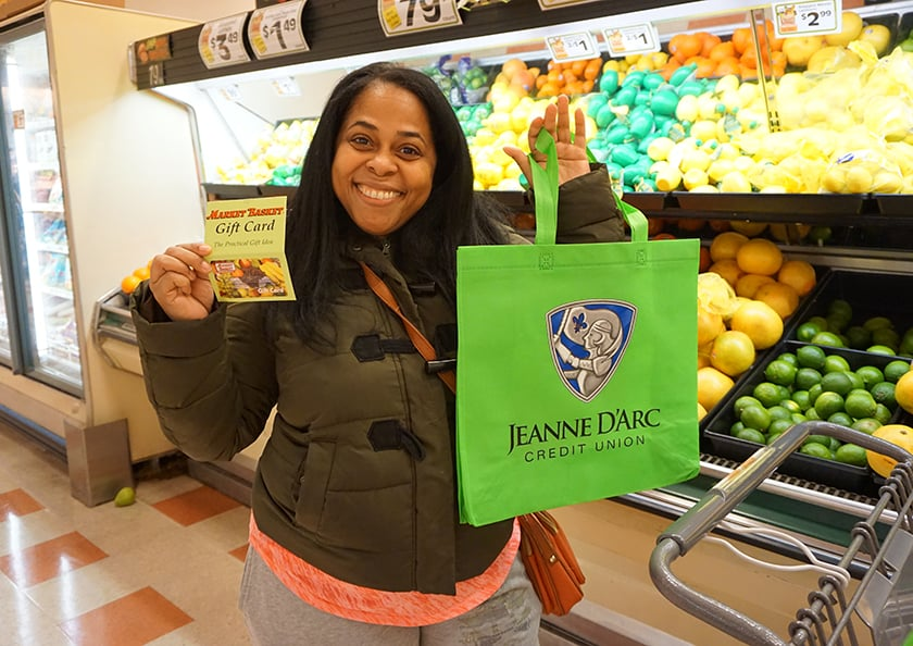 A woman in a grocery story holding a Jeanne D'Arc Credit Union bag